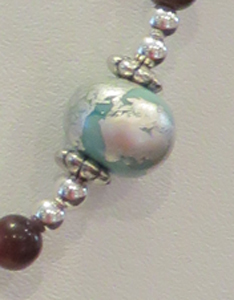 Silver leaf on a green glass bead by Gayle Stringer