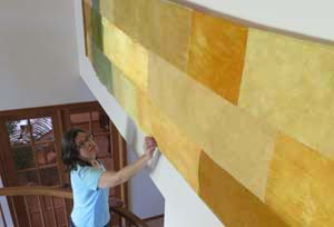 Anne Bossert checks the drape of her cotton and silk fiber art.