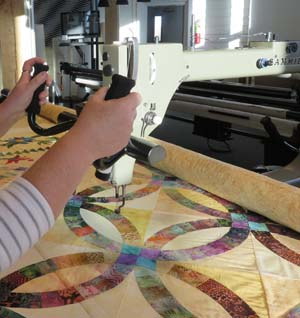 A customer guides a longarm quilting machine at Jukebox Quilts