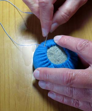 Becky Margenau wraps a stone with felt.