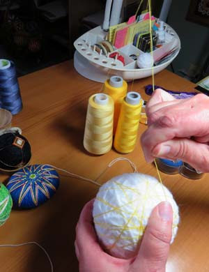 Becky Margenau wraps thread around a ball already wrapped with yarn as she prepares the ball for temari designs.