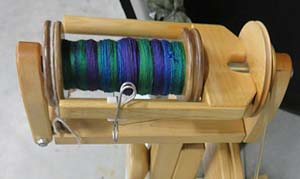 A bobbin of silk and merino wool dyed and spun by Kimber Baldwin